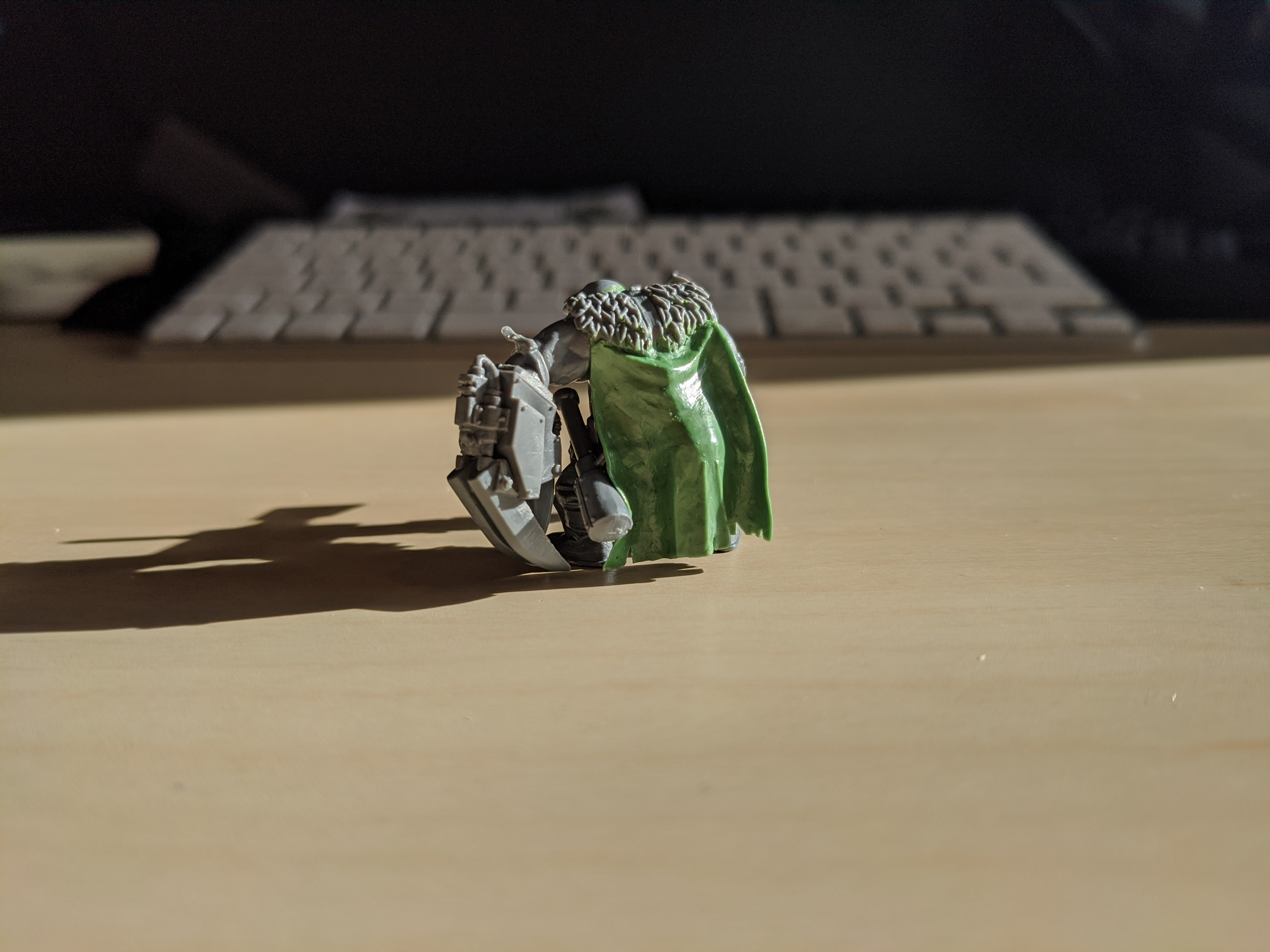 An Ork miniature with a custom sculpted cloak with battle damage
