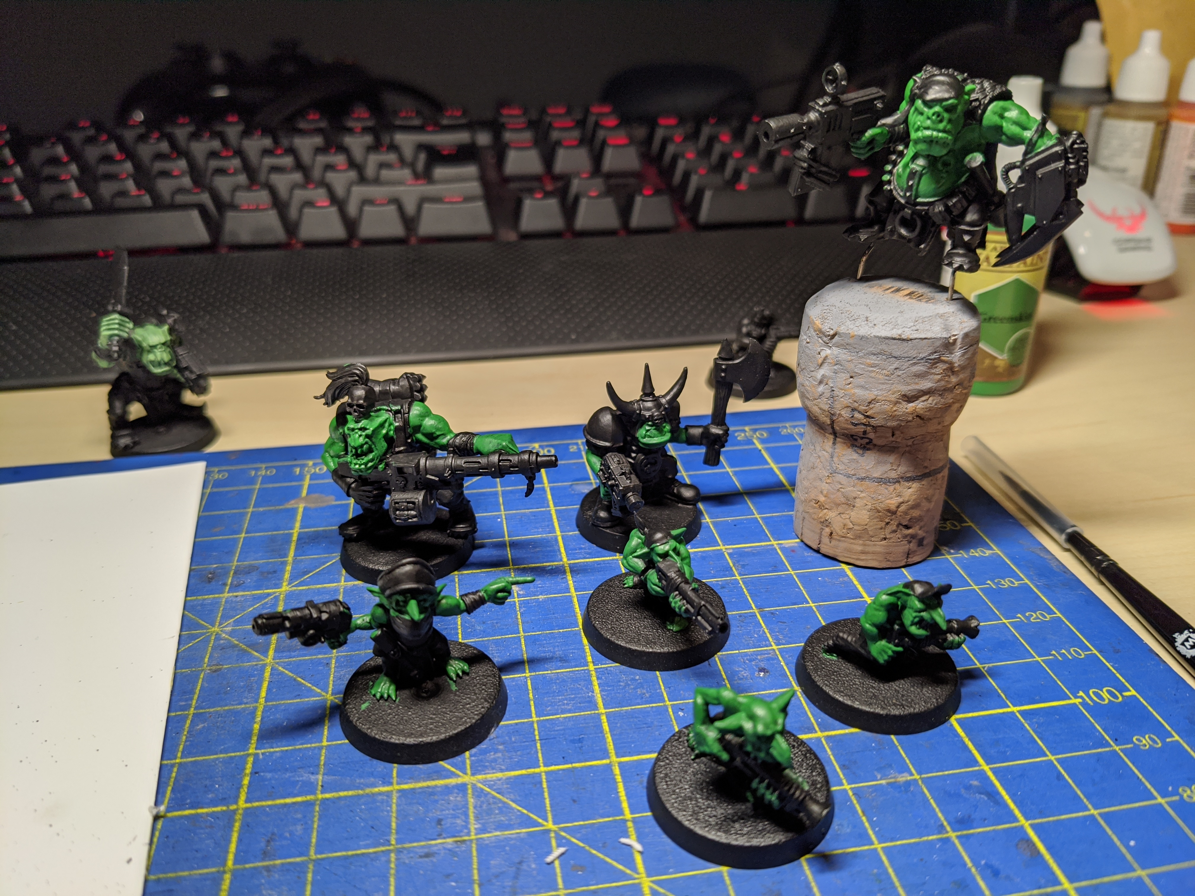 A collection of Ork models with skin painted green